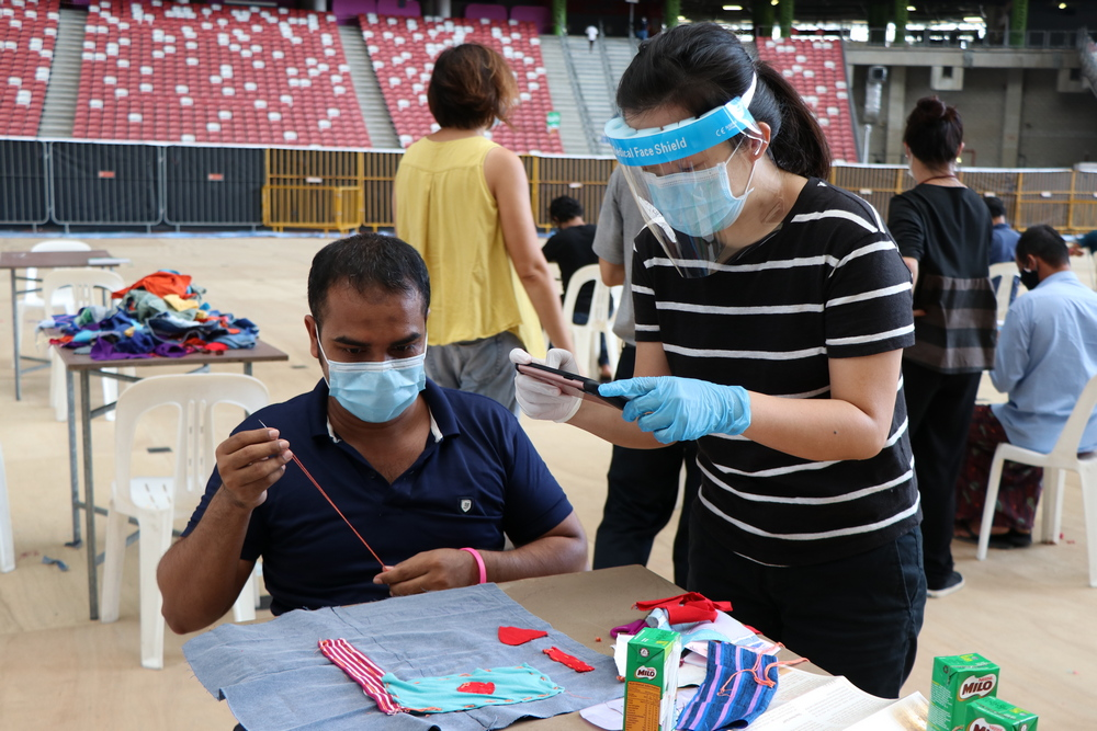 Representative of Singapore International Foundation, Ms Ng (on the right with a face shield) is joining the migrant workers in sewing. (Photo by Mulias)