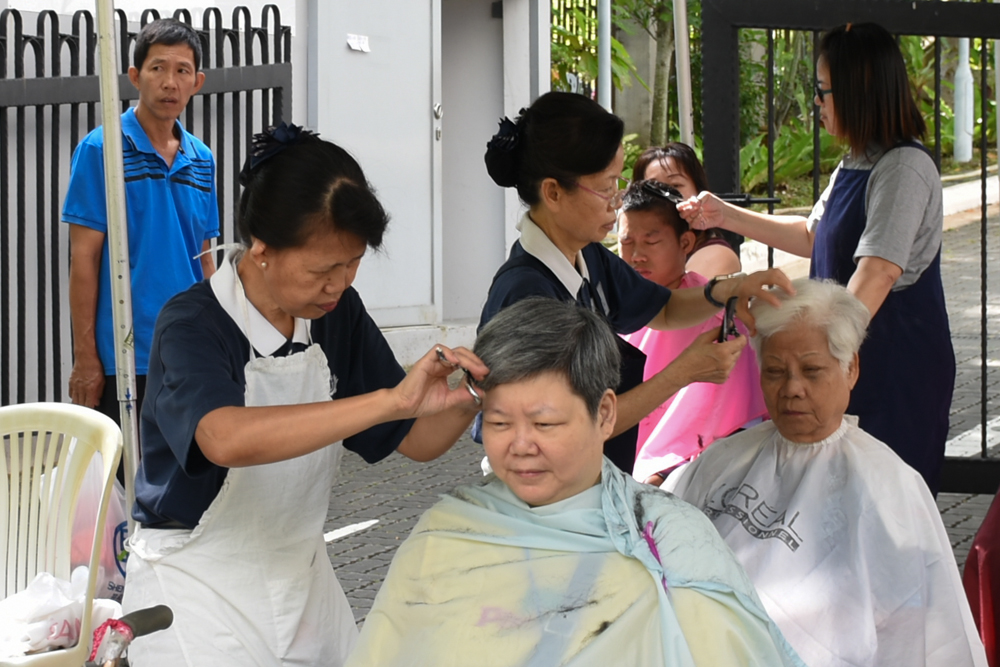 Aid recipients getting their free haircuts outside the Jing Si Hall before the celebration commences (Photo by Audrey Phang)