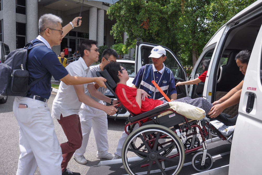 Volunteers assisting a wheelchair bound aid beneficiary to get off the car (Photo by Peter Andrew)