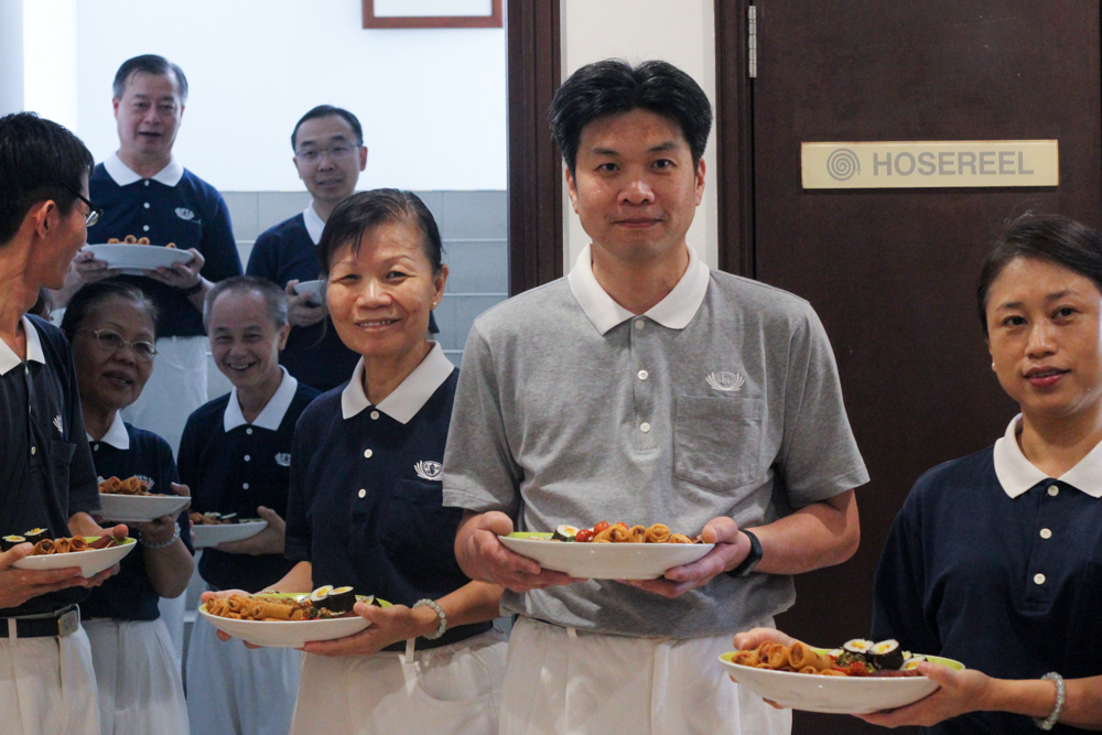 Volunteers queuing up to enter the main hall to serve the dishes (Photo by Audrey Phang)