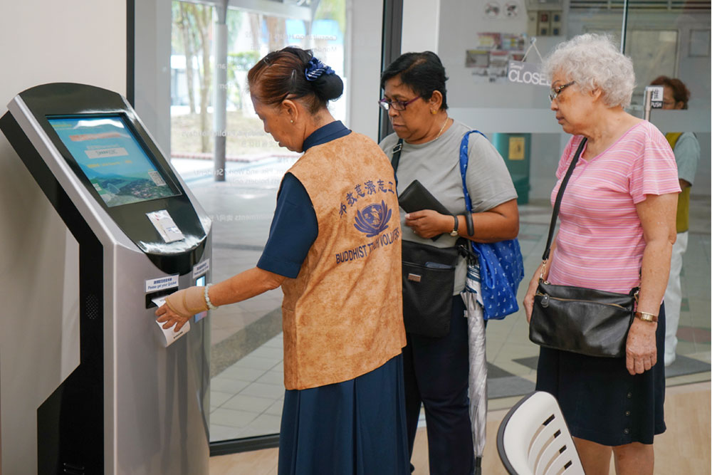 A digital kiosk at the free clinic allows patients to scan their ID cards and obtain their queue numbers. (Photo by Chan May Ching)