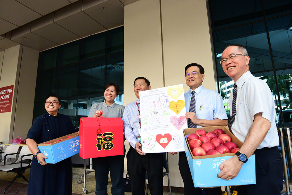 Tzu Chi CEO Mr Low Swee Seh (second from right) and volunteer representatives handing over care packages, fruit baskets and a large greeting card to Associate Professor Chin Jing Jih, the Chairman of the Medical Board of TTSH. (Photo by Wong Twee Hwee)