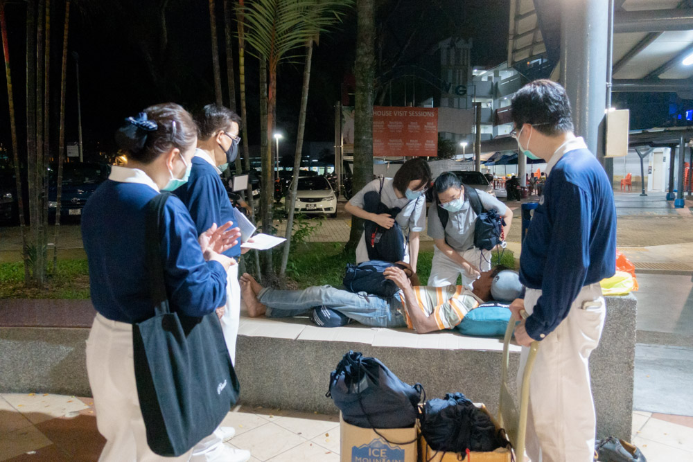 Tzu Chi staff and volunteers handing out care packages to stranded Malaysian workers who spent their nights beneath HDB flats. (Photo by Pang Lun Peng)