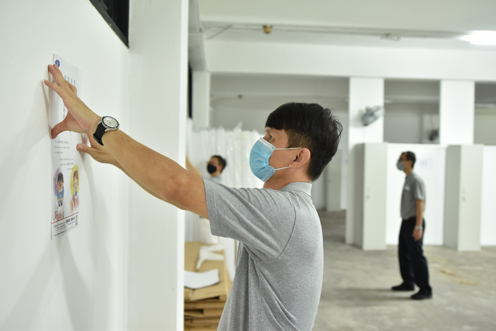 Volunteers are pasting Jing Si Aphorisms posters in unfurnished bedrooms. (Photo by Lai Tong Heng)