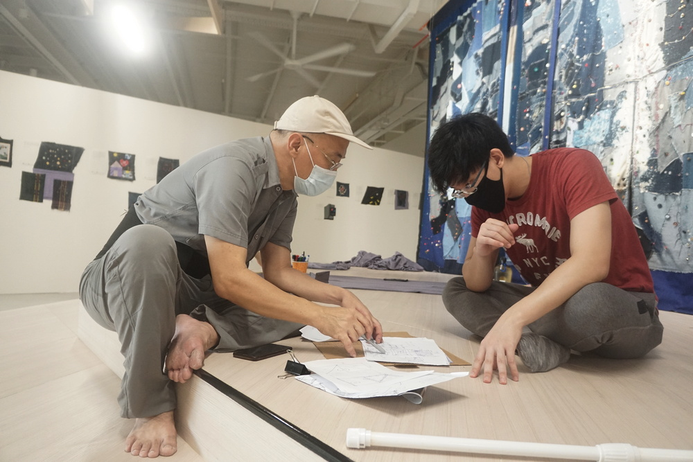 Jimmy Ong having a discussion with a Tzu Ching on the frame and design of the artwork. (Photo by Bernard Ng Jia Han)